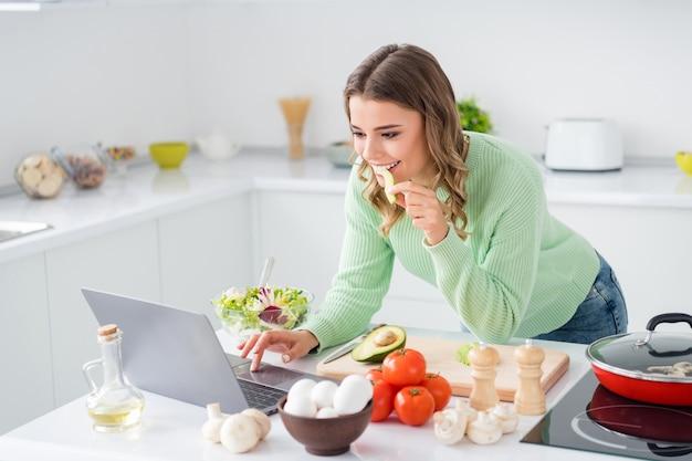 Portret van mooi meisje dat avocado-kokende groenten eet met behulp van laptop