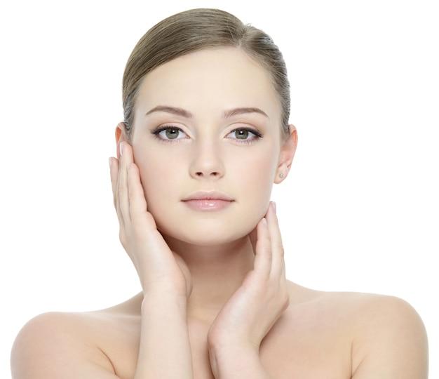 Portret van mooi meisje dat haar mooi gezicht met gezonde huid streelt