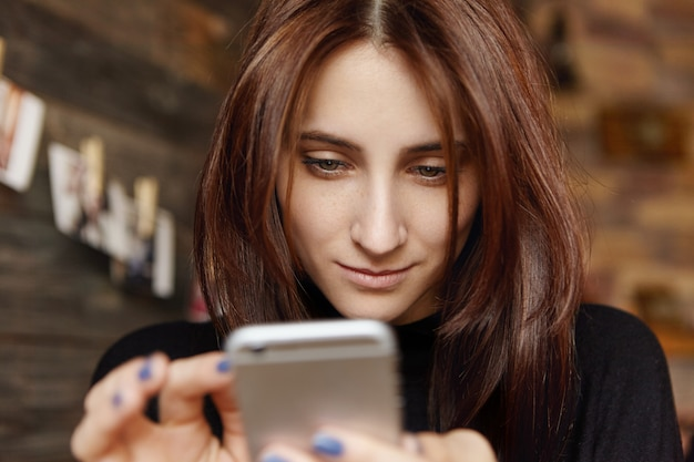 Portret van mooi meisje dat het artikel van de de mobiele telefoonlezing van het aanrakingsscherm op online tijdschrift gebruikt of internet doorbladert terwijl het wachten op cappuccino, die rust alleen bij restaurant heeft. selectieve focus op gezicht