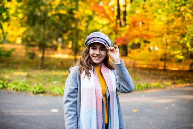 Portret van mooi meisje dat onderaan de de herfststraat loopt.