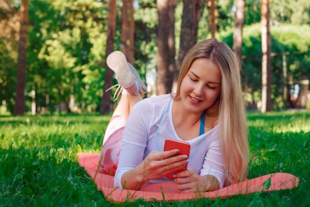 Portret van mooi meisje dat op carrymate ligt en haar celtelefoon houdt. zij lacht