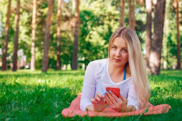 Portret van mooi meisje dat op gras ligt en haar celtelefoon houdt