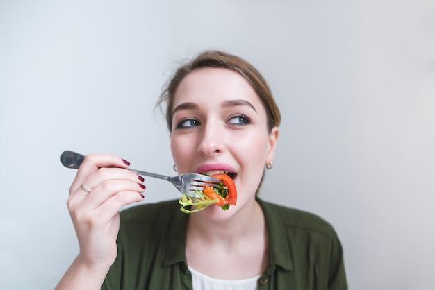 Portret van mooi meisje dat salade met vork op grijze achtergrond eet. mooie vrouw eet gezonde maaltijd.