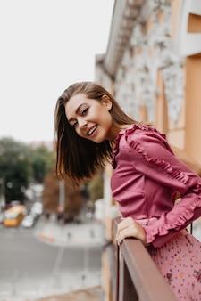 Portret van mooi meisje dat uit achter balkonleuning gluurt. jonge reiziger met kort haar is blij dat ze de nieuwe oude stad ziet