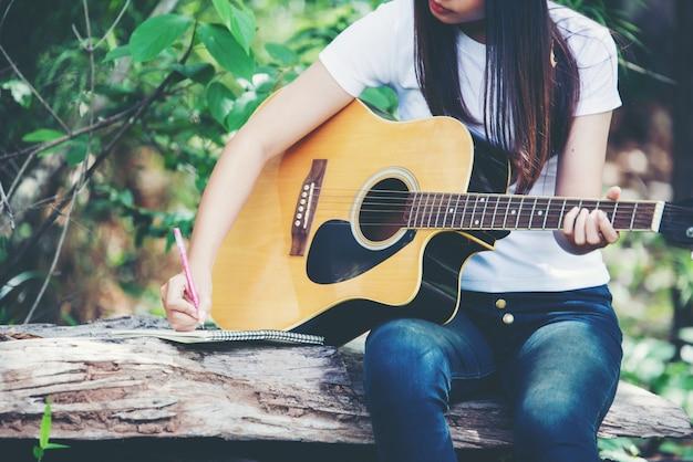 Portret van mooi meisje die de gitaar met het schrijven bij aard spelen