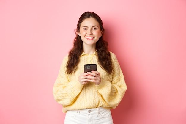 Portret van mooi meisje die mobiele telefoon houden en glimlachen, online winkelen, sociale media-app gebruiken, die tegen roze muur in vrijetijdskleding staan.