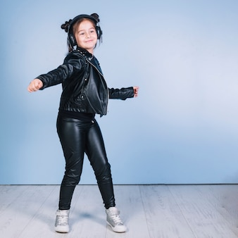 Portret van mooi meisje die modieuze zwarte uitrusting dragen die tegen blauwe muur dansen