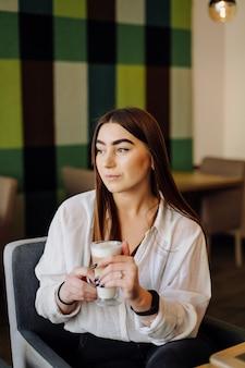Portret van mooi meisje, hete thee of koffie drinken in een café met haar mobiele telefoon.