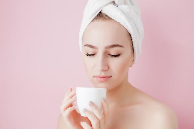 Portret van mooi meisje in badjas met een kopje thee, ontspanningsconcept blonde vrouw die badjas en handdoek op hoofd draagt na douche. kuuroordvrouw in badjas en tulband.