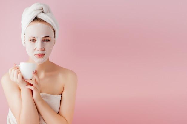 Portret van mooi meisje in badjas met een kopje thee, ontspanningsconcept blonde vrouw die badjas en handdoek op hoofd draagt na douche