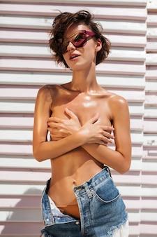 Portret van mooi meisje in denimborrels en zonnebril. mooi meisje permanent en haar borst bedekt met handen op het strand