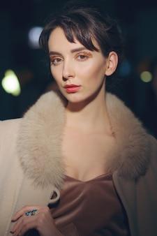 Portret van mooi meisje in jas met bontkraag poseren in donkere kamer met lichten aan