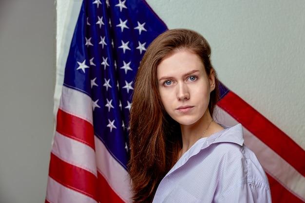 Portret van mooi meisje in overhemd op amerikaanse vlag dichte omhooggaand als achtergrond