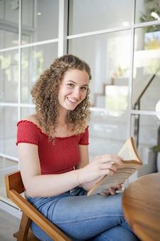 Portret van mooi meisje. lachende vrouw thuis een boek lezen study concept leesboek