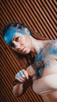 Portret van mooi meisje met blauwe gezichts bodyart met pailletten. de kunstenaar tekent body art op zichzelf