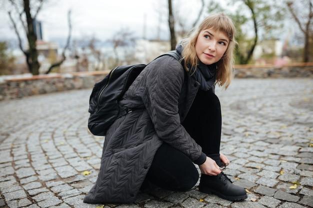 Portret van mooi meisje met blond haar dat bedachtzaam opzij kijkt terwijl gebogen op straat om de schoenveters te binden