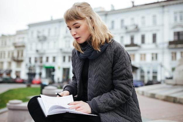 Portret van mooi meisje met blond haar, zittend met laptop in de hand op straat in de stad