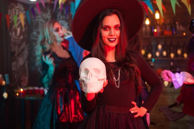 Portret van mooi meisje met een grote hoed verkleed als een heks voor halloween-feest. enge heks die een menselijke schedel vasthoudt en naar de camera kijkt
