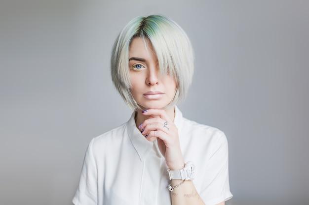 Portret van mooi meisje met grijze korte haarstijl op grijze achtergrond. ze draagt een witte jurk en lichte make-up. een pony bedekt de helft van het gezicht. haar hand raakt haar gezicht.