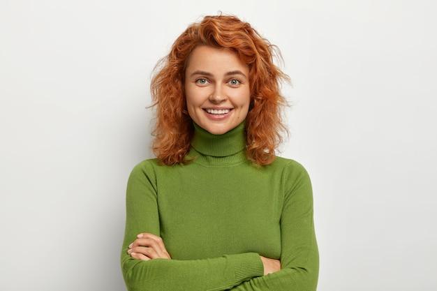 Portret van mooi meisje met kort gemberhaar, kijkt met een gelukkige ontspannen uitdrukking