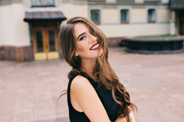 Portret van mooi meisje met lang krullend haar poseren op straat