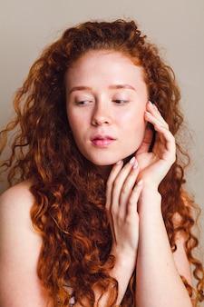Portret van mooi meisje met lang krullend rood haar geen make-up geen retoucheren jong huidverzorgingsconcept