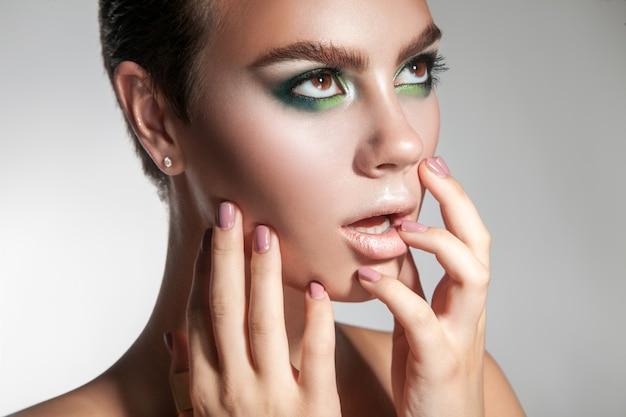 Portret van mooi meisje met make-up met handen en gezonde huid in de studio
