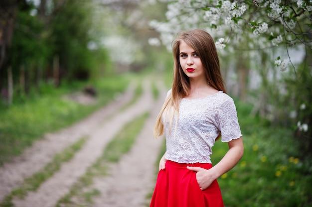 Portret van mooi meisje met rode lippen bij de tuin van de de lentebloesem, slijtage op rode kleding en witte blouse.