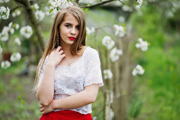 Portret van mooi meisje met rode lippen bij de tuin van de de lentebloesem, slijtage op rode kleding en witte blouse