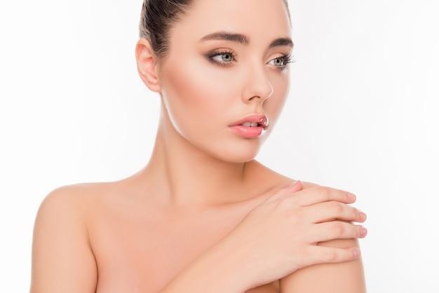 Portret van mooi meisje met sensuele huid aan haar schouder te raken