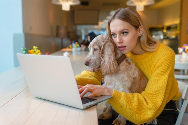 Portret van mooi meisje met verrast gezicht dat haar aanbiddelijk puppy houdt en laptop met behulp van