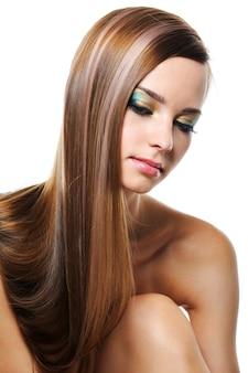 Portret van mooi meisje met vlot glanzend lang haar dat op wit wordt geïsoleerd