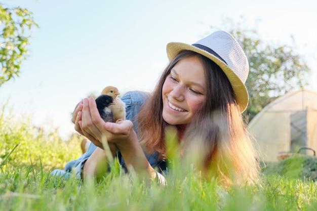 Portret van mooi meisje op boerderij met twee pasgeboren kuikens in de hand