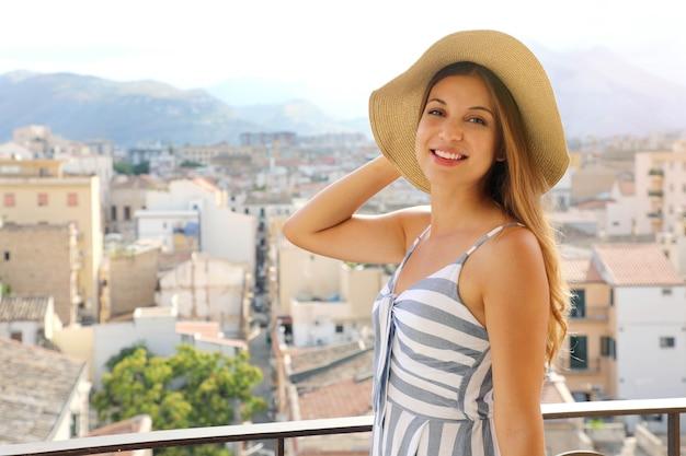 Portret van mooi meisje op terras in palermo met stadsgezicht op de achtergrond, sicilië, italië