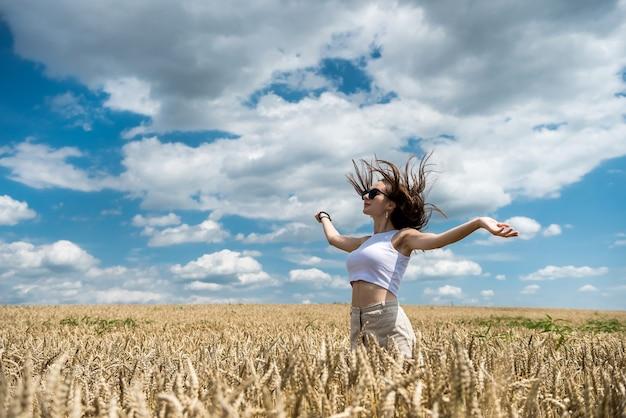 Portret van mooi meisje poseren in een tarweveld genieten van zomertijd. vrijheid