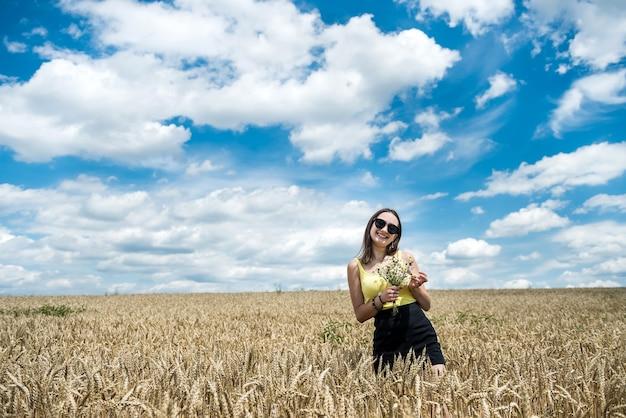 Portret van mooi meisje poseren in tarweveld genieten van zomertijd. vrijheid