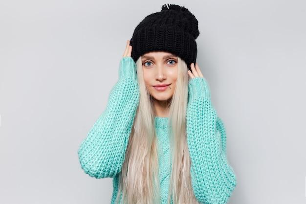Portret van mooi meisje tegen witte muur. jonge vrouw, gekleed in blauwe trui en zwarte hoed.