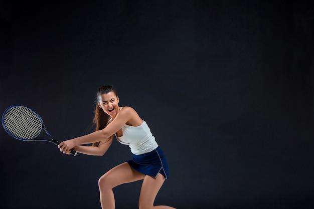 Portret van mooi meisje tennisser met een racket op donkere muur