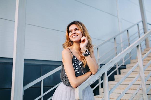 Portret van mooi model in grijs overhemd dat op leuning op treden leunt. ze glimlacht naar haar kant.