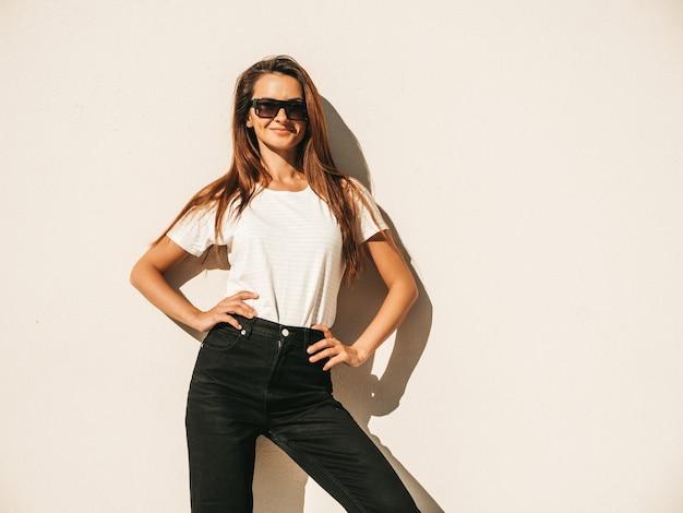 Portret van mooi model in zonnebril. vrouw gekleed in zomer hipster wit t-shirt en jeans. trendy meisje poseren in de buurt van muur in de straat