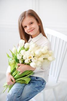 Portret van mooi mooi meisje dat met witte bloementulpen op stoel zit