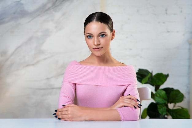 Portret van mooi mooi meisje, student, jonge prachtige aantrekkelijke vrouw zittend aan tafel in kantoor