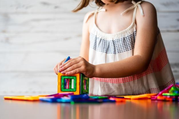 Portret van mooi nadenkend meisje dat de kleurrijke uitrusting van magneet plastic blokken speelt,
