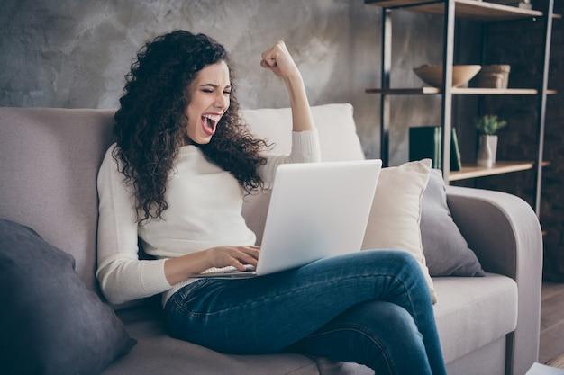 Portret van mooi ogende aantrekkelijke mooie vrolijke meisje met laptop vieren prestatie in moderne loft industriële stijl interieur kamer binnenshuis