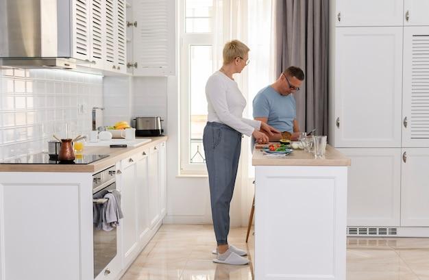 Portret van mooi ouder paar die samen gelukkige hogere vrouw koken die ontbijt voor haar koken