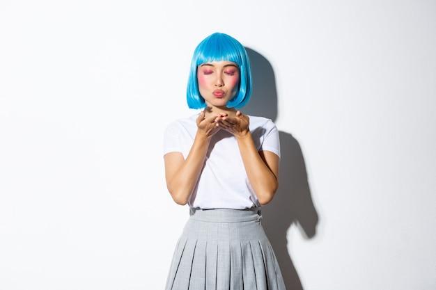 Portret van mooi popmeisje in blauw overhemdspruik waait luchtkus bij camera, sluit ogen en staand romantisch.