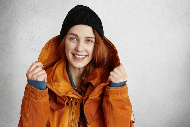 Portret van mooi roodharig meisje gekleed in modieuze rode winterjas en zwarte hoed