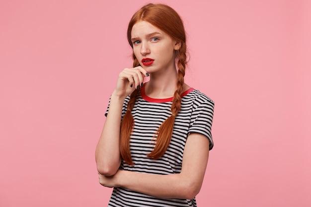 Portret van mooi roodharig meisje met twee vlechten houdt vuist bij de kin en kijkt sceptisch, met verdacht en wantrouwen, twijfelachtig, geïsoleerd op roze muur