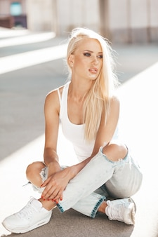 Portret van mooi schattig blond meisje in witte t-shirt en jeans die in openlucht stellen. leuke meisjeszitting op asfalt op de straat