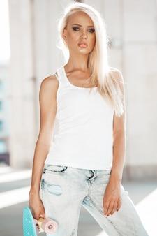 Portret van mooi schattig blond meisje in witte t-shirt en jeans die in openlucht stellen. meisje met blauw stuiverskateboard op de straat